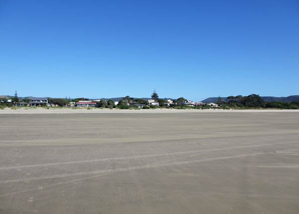 Houses line the beach in Ahipara (New Zealand)